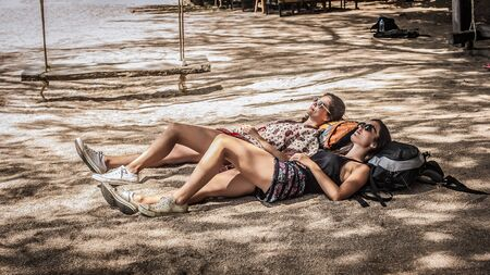 Two girls friends backpackers enjoying and lying on their ranches on the tropical beach sand in the shade