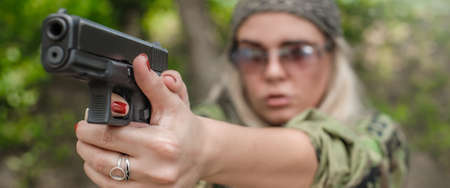 Attractive soldier woman practice shooting and gun point aim to attacker. Close-up pistol pointing front view. Nature outdoor