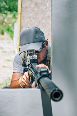 Rifle machine gun combat shooting training from behind and around cover or barricade. Advanced fighting tactical shooting courses on shooting range Reklamní fotografie