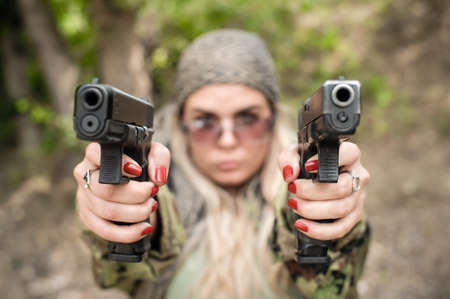 Attractive soldier woman practice shooting with two gun and gun point aim to attacker. Abstract close-up pistol wide angle pointing front view. Nature outdoor