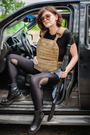 Beautiful and attractive female military soldier with shotgun pump gun. Woman with weapon