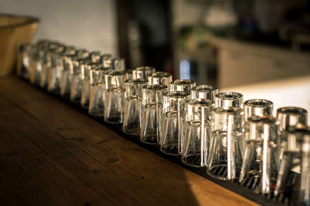Row of clean shiny glasses lined up on a bar counter in a nightclub ready for the barmen to use to serve alcoholic beverages