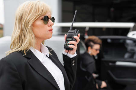 Female Bodyguard. Celebbrity bodyguard and VIP protection services. Black suit and walkie talkie. Security guard service