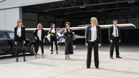 Famous female celebrity with bodyguards surrounded. VIP security agents and close protection officers