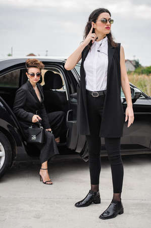 Female Bodyguard. Celebbrity bodyguard and VIP protection services. Black suit and handsfree. Security guard service