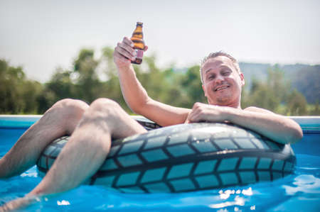 Happy young man with inflatable rings drink beer, relaxing and enjoying summer in swimming pool