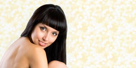 pretty woman with long straight black hair looking at camera, isolated on gold background photo