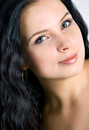 Beautiful young woman face. Black hair. Close up. photo