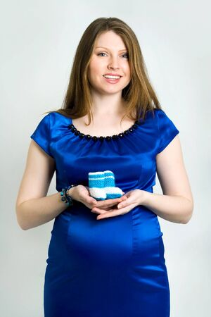 Young mother holding blue knitted baby shoes photo