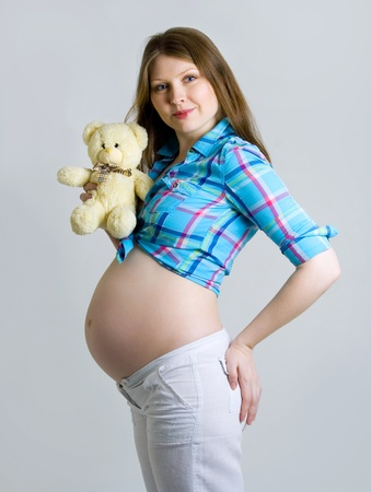 Pregnant woman caressing her belly with a bear in his hand and checked shirt Stock Photo