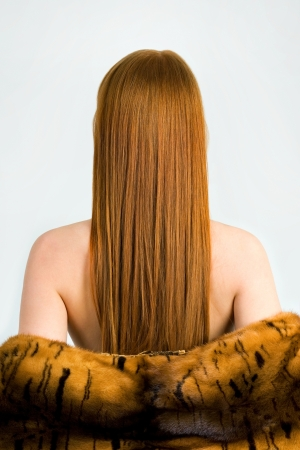 Beautiful young red-haired woman with long beauty straight hair. With a coat on the bare shoulders photo