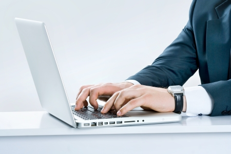 Close-up of male hands typing on laptop keyboard photo
