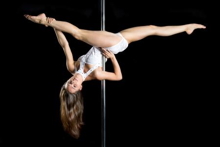 Jonge sexy vrouw oefening pole dance tegen een zwarte achtergrond