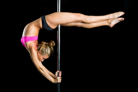 nude gymnast: Young sexy woman exercise pole dance against a black background