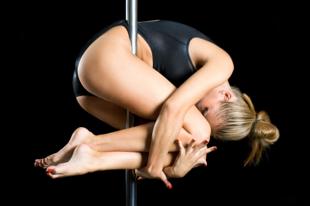 Young sexy woman exercise pole dance against a black background
