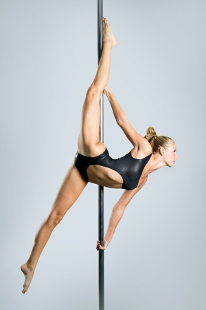 nude gymnast: Young sexy woman exercise pole dance against a gray background