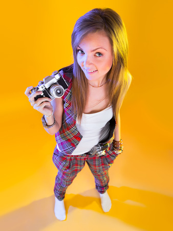 Funny girl in full growth with a camera in hand. Pretty looking at viewer. Isolation on a yellow background.
