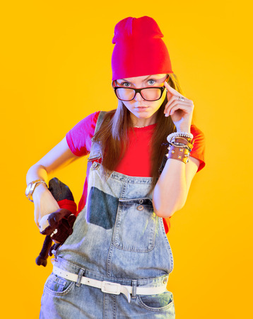 looking at viewer: Portrait of funny girl in glasses and red caps. Seriously looking at viewer. Isolation on a yellow background. Stock Photo