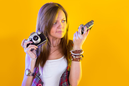 Portrait of funny girl with two cameras in their hands. Stares at the camera. Isolation on a yellow background. Stock Photo