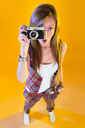 Funny girl in full growth with a camera in hand. Surprised by Samer looking at viewer. Isolation on a yellow background. Stock Photo