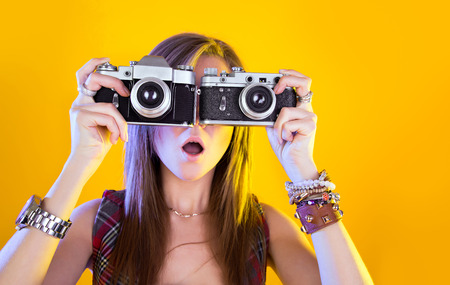 Portrait of funny girl with two cameras in their hands. Surprised by Samer looking at viewer. Isolation on a yellow background.