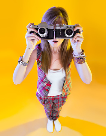 Funny girl in full length with two cameras in their hands. Surprised by Samer looking at viewer. Isolation on a yellow background.