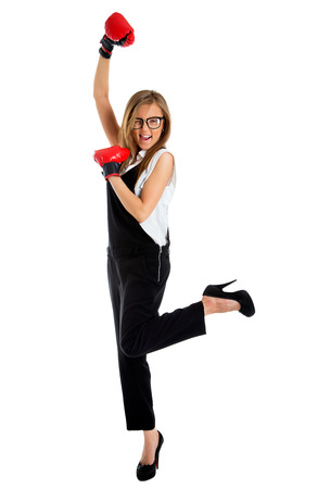 winning business woman: Winning business woman celebrating wearing boxing gloves and business suit. Stock Photo