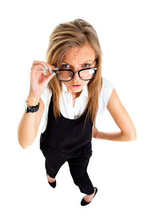 disdain: Suspicious upset angry and funny secretary taking off her glasses standing isolated on white background in high angle. Stock Photo