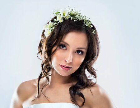 Mooie bruid draagt witte trouwjurk met bloemen op haar hoofd Stockfoto