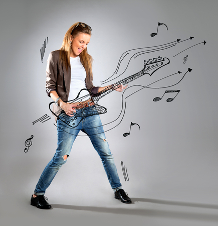 Woman listening to music on mp3 player dancing playing air guitar. Funny happy portrait of business woman isolated on white background in full length.