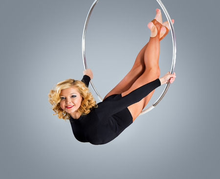 somersault: Plastic beautiful girl gymnast on acrobatic circus ring in fleshcolored suit. Aerial ring. Stock Photo