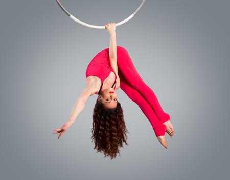 Plastic mooi meisje turnster op acrobatische circus ring in fleshcolored pak. Aerial ring. Stockfoto