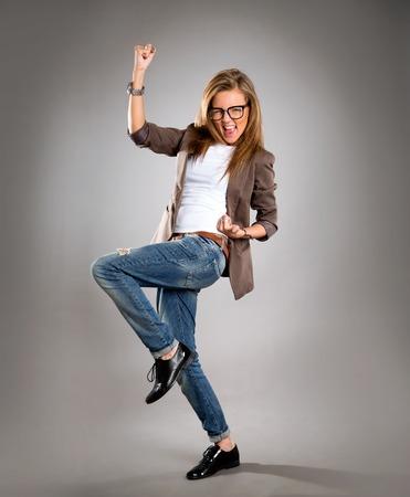 Succesvolle zakenvrouw met armen omhoog geïsoleerd op een grijze achtergrond