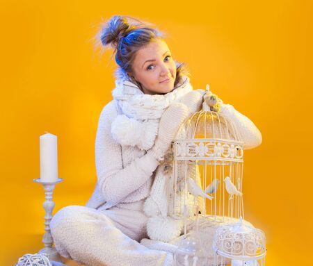 Portrait of funny girl in a Christmas suit with cell in hand on a yellow background
