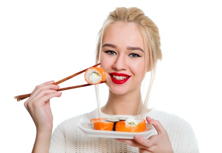 sushi: Beautiful woman holding sushi with a chopsticks, isolated