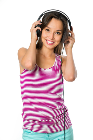 Young woman with headphones listening music .Music teenager girl dancing against isolated white background Stock Photo