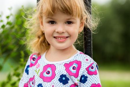 chicas sonriendo: Pequeña escalada Feliz niña en el patio al aire libre Foto de archivo