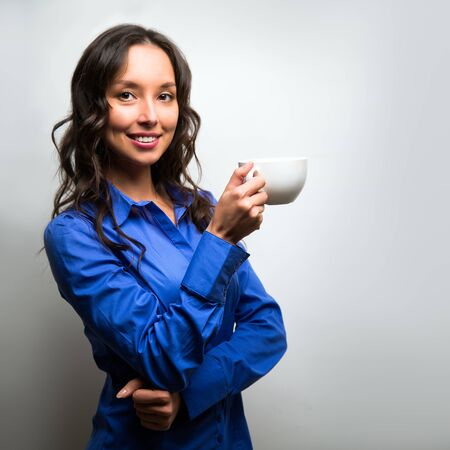 Business woman portrait with cup and saucer, isolated. Female model with long hair. Coffee break.