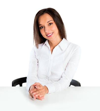 spokesperson: Woman sitting at table smiling at camera. Beautiful young businesswoman mixed Asian Chinese white Caucasian. Stock Photo