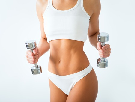Torso of a young fit woman lifting dumbbells on white background Stock Photo