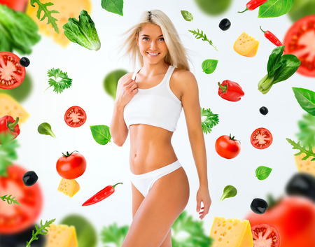 muscular body: Sports girl on a white and vegetables background Stock Photo