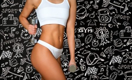 Torso of a young fit woman lifting dumbbells on black and draw background Stock Photo