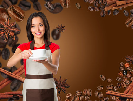 Coffee serving waitress. Young asian barista woman smiling showing cup of coffee. Isolated on brown background. Focus on waitress.