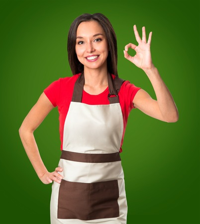 gesture: Cooking and food concept - smiling female chef, cook or baker with fork showing ok on green background Stock Photo