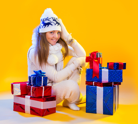make a gift: Christmas Woman. Beautiful New Year and Christmas Gift Holiday Make up. Beauty Girl with Colorful Makeup, Hair, Gift and Accessories. Happy and funny Woman. Emotions. Yellow background
