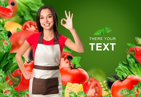 Cooking and food concept - smiling female chef, cook or baker with fork showing ok sign over falling vegetables on green background