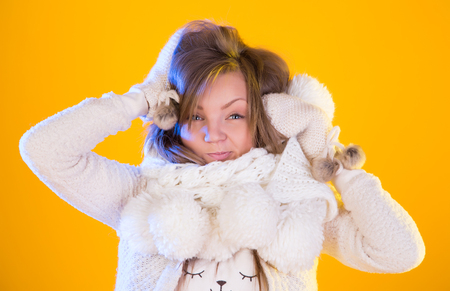 Winter Christmas Girl. Beautiful Woman Blowing Snow, isolated on yellow