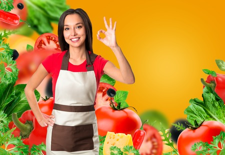 Cooking and food concept - smiling female chef, cook or baker with fork showing ok sign over falling vegetables on yellow background