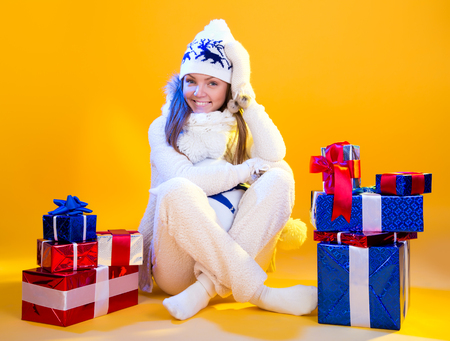 Christmas Woman. Beautiful New Year and Christmas Gift Holiday Make up. Beauty Girl with Colorful Makeup, Hair, Gift and Accessories. Happy and funny Woman. Emotions. Yellow background