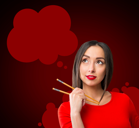 Young woman holding sushi with a chopsticks, isolated on red Stock Photo